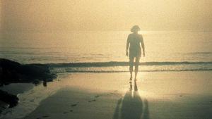 Nainen kävelee hiekkarannalla auringonlaskun aikaan.