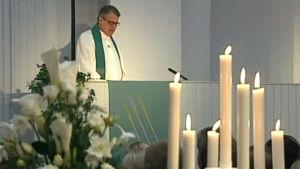 Pappi pitää Myyrmannin pommi-iskussa kuolleille muistotilaisuutta Myyrmäen kirkossa 20.10.2002, ohjelmasta Muistohartaus Myyrmäen kirkossa Vantaalla.