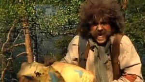 Rölli (Allu Tuppurainen) nauraa ohjelmassa Rölli suunnistaa (1993)
