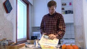 Mies selaa sanomalehtipinkkaa, ohjelmasta Media ja me (2004)