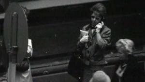 Nainen vastaa kadulla olevaan puhelimeen.