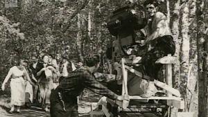 Elokuvan filmausryhmä järven rantamaisemassa. Kuvaaja ja kamera puisen telineen päällä.