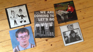 Pertti Kurikan Nimipäivät boken We are coming to let´s go samt fyra vinylsinglar av bandet på ett trägolv