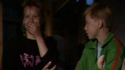 Kaksi lasta, joista toinen pitää kättään suullaan ja toinen katsoo häntä.