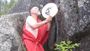 Vahan mies harmaassa parrassa, punaisessa kaavussa lyö shamaanirumpua metsässä.