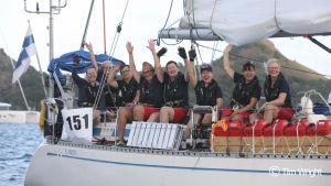 Åtta kvinnor i en segelbåt. De vinkar och är glada. Plats: Karibien, vid vatten