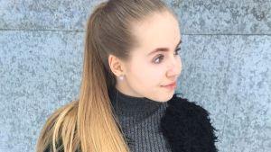 Elvira Nyrönen står framför en vägg, hon är finalist i MGP.