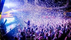 Juhlivaa konemusiikkikeikkayleisöä jonka päälle sataa konfetteja. Reunassa näkyy myös keikan esittävä DJ Headhunterz.