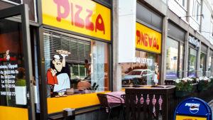 Pizzeria med uteservering på gatan.