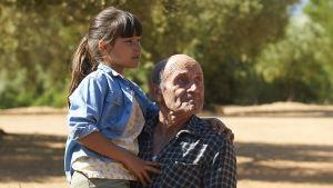 Alma (Inés Ruiz) i famnen på sin farfar Ramón (Manuel Cucala).