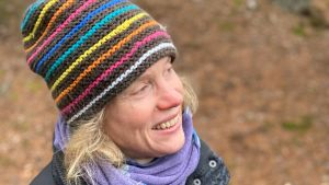 Susanne Österlund-Pötzsch i radig mössa mot en höstbrun bakgrund.