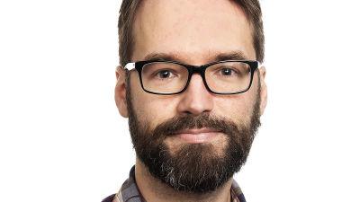Man med skäg och glasögon mot vit bakgrund.