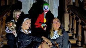Au pairit Irlannissa sarjan henkilöt Ada, Nea, Igi ja Luna istuvat halloween-asuissa Loftus Hall -kummitustalon portailla hämärässä.