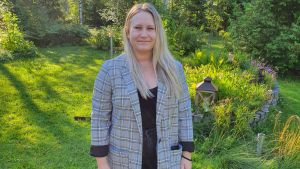 Melissa Ekström står på en gräsmatta och ser in i kameran.