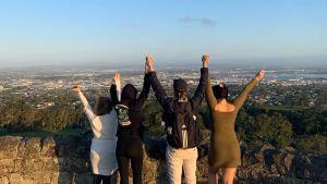 Au pairit seisovat selin kameraan päin One Tree Hillin näköalapaikalla vierekkäin kädet kädessä, kädet taivasta kohti