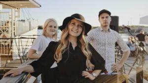 Tre personer ser in i kameran. Kvinnan längst fram har en svart klänning och hatt och de två bakom har vita kläder.
