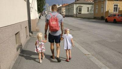 Pappa Nicklas promenerar längs en trottoar med ett barn i var hand.