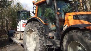 Traktor med en liten grävmaskin på släp.