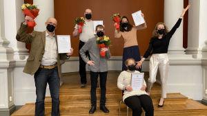 En grupp människor står med prisdiplom och blommor i händerna.