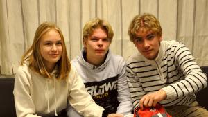 De tre ungdomarna sitter på en soffa och kollar i ryggsäcken på bordet framför.