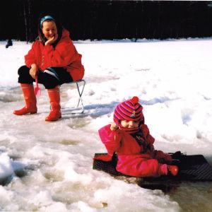 Monitaituri Noora Västinen lapsena pilkillä äitinsä kanssa. Noora istuu pulkassa.