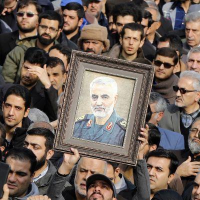 En folkmassa bär en tavla som avbildar Qassim Suleimania.