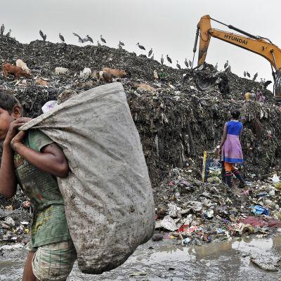 Lapsia kaatopaikalla keräämässä jätteitä.