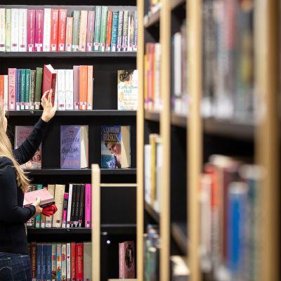 Nainen katselee kirjoja Tikkurilan kirjastossa Vantaalla