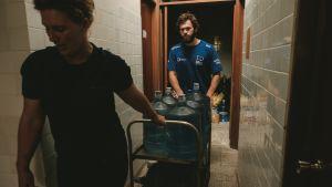 Vesipulloja lastataan lauttoihin
