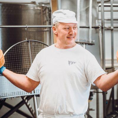 Juustomestari Peter Dörig pitää käsissään isoja juustokiekkoja.