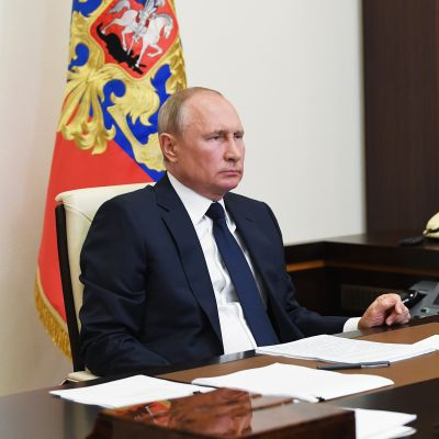 Vladimir Putin istuu työpöytänsä ääressä.