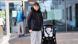 En man står bredvid en barnvagn med ett litet barn i.