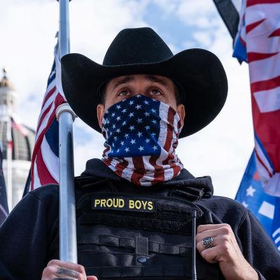 """En man i cowboyhatt står framför Capitolium i USA. Han bär en scarf med USA:s flagga över ansiktet, på hans jacka står det """"Proud boys""""."""