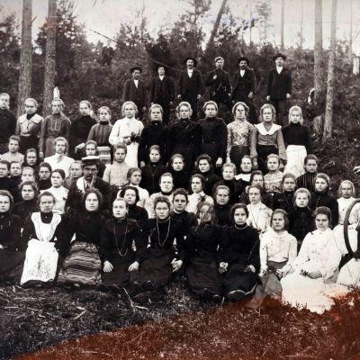 """Voikkaan tehtaan paperisalin työläisiä, jotka osallistuivat vuonna 1904 """"Schmitzin lakkoon"""", istuvat metsässä ryhmäkuvassa.."""