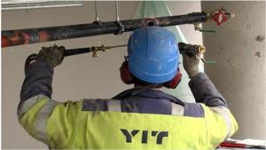 Man i guljacka arbetar med rör i taket
