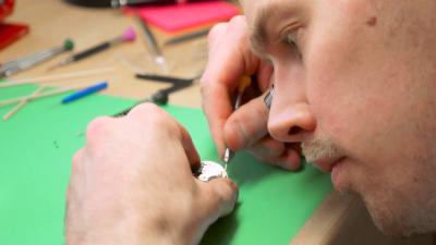 Närbild av urmakare Eric Wikman som med specialverktyg reparerar ett ur.
