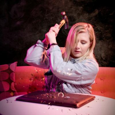 Ammattihakkeri Laura kankaala hakkaa vasaralla kannettavaa tietokonetta.