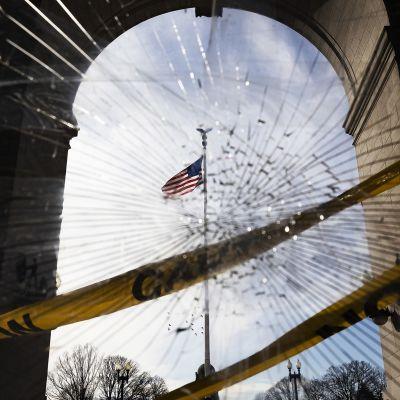 Yhdysvaltain lippu kuvattuna Capitolin säröillä olevan ikkunan läpi.