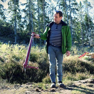 Danne Mattsson intill ett kalhygge med en planteringsmaskin för småplantor.