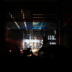 En butik lyses upp med en mopedlampa på grund av strömavbrottet.