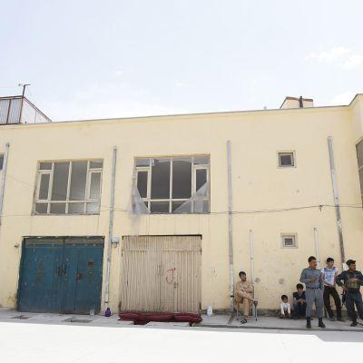 Turvallisuusjoukkojen jäseniä sekä lapsia seisoo ja istuu keltaisen rakennuksen edustalla.