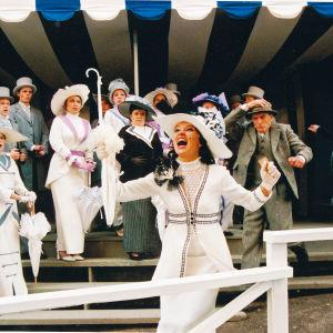 Samppalinnan kesäteatterin My Fair Lady -musikaalin laukkakilpailun kohtaus, jossa naiset hienoissa valkoisissa hatuissaan ja puvuissaan, miehet harmaissa shaketeissaan ja silinterihatuissaan.