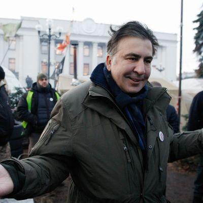 Mihail Saakashvili levittelee käsiään kuvan etualalla, hänen takanaan näkyy muutamia muita miehiä ja Kiovan parlamenttirakennus.