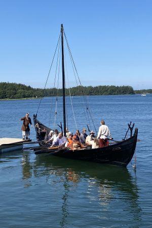 Vikingaskeppet Sotka med ett tiotal roddare lägger till vid en brygga i skärgården.
