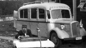 """Mies soittaa kannelta ja taustalla """"ääniauto Tapernaakkeli, Yleisradion ensimmäinen auto, jossa oli aluksi mekaaniset levytyslaitteet ja myöhemmin magneettiset. Kyljissä kovaääniset radion merkin kohdalla. Katolla kaiteet selostajaa varten""""."""