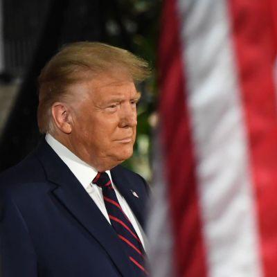 Donald Trumt står bakom USA:s flaggor.