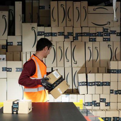 Työntekijä lastaa paketteja kuljetukseen Amazonin logistiikka- ja jakelukeskuksessa.