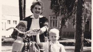 Eero Hämeenniemi lapsena taluttamassa polkupyörää yhdessä äitinsä ja siskonsa Irman kanssa.