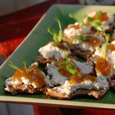 Ett fat med små knäckebrödssmörgåsar toppade med ost och fikonmarmelad.