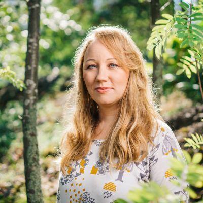 Kuvassa Havaintoja ihmisestä -radiosarjan toimittaja Satu Kivelä. Ympärillä aurinkoinen metsä.
